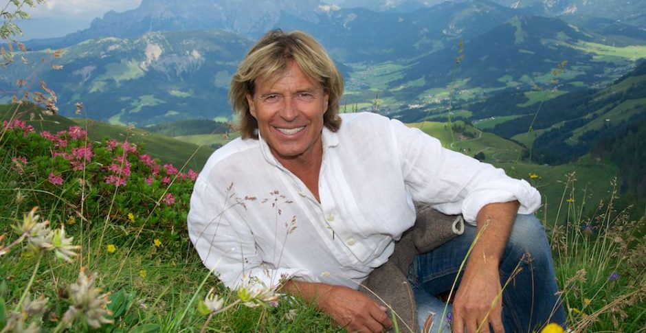 """Download von www.picturedesk.com am 19.08.2016 (15:38). The Austrian singer Hansi Hinterseer sitting amongst the alpine flowers on a pause from a hiking from the Alpine House on the Kitzbueheler Horn to Hornkoepflhuette in Kitzbuehel in Tyrol, Austria, 9 July 2015. His new album """"Gefuehle"""" (lt: 'Feelings') is due to be released on 10 July 2015. Photo: Ursula Dueren/dpa - 20150709_PD11190"""